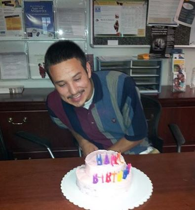 A young man getting a special birthday cake delivery at the Project Everlast Omaha office.