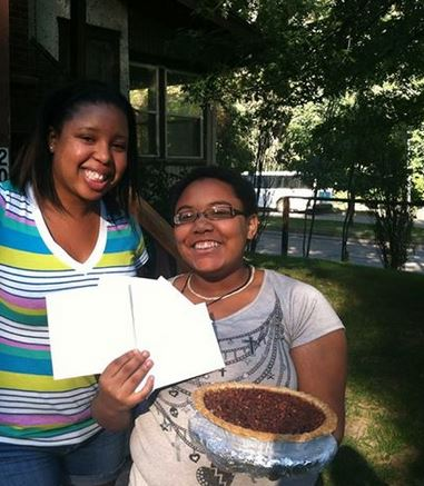 Schalisha giving a homemade pecan pie, baked by a volunteer, to a young woman on her birthday.