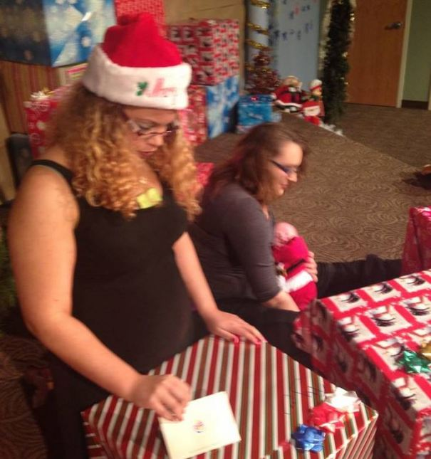 Ty from the Omaha council opening her gift near the massive stack of packages.
