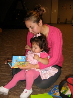 One of the young mothers Nancy works with reading to her toddler.