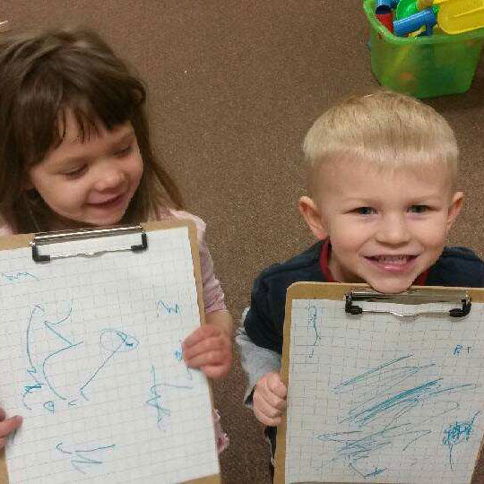 Two children who attend Kinder Haus hold up their newest artwork.