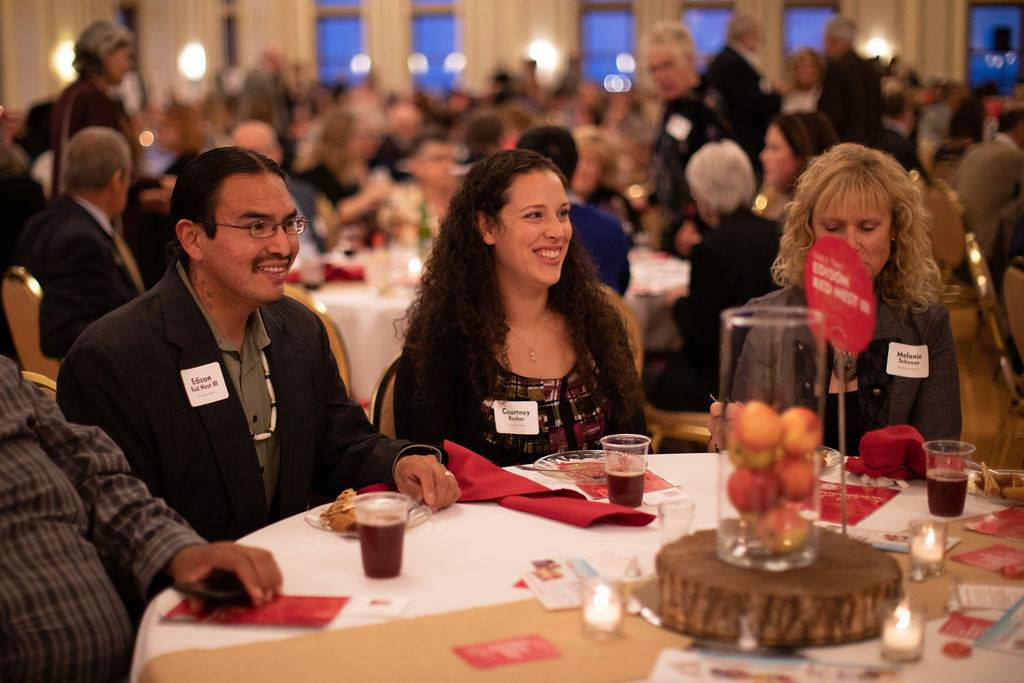 Edison Red Nest (left) now has a seat at many tables as an indispensable community staple. Here he is at Nebraska Appleseed's Good Apple Award Ceremony!